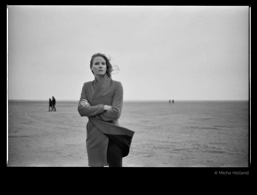 Woman with coat on the beach by Micha Holland. The photo shows Cate Martin wearing a coat. With crossed arms she is standing on the beach staring into the distance.