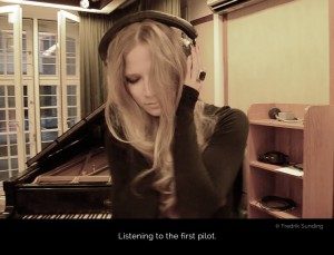 Cate Martin in the recording room at Tambourine Studios listening to the first pilots with headphones on.