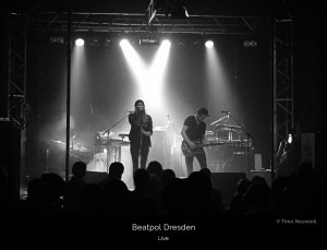 Ivy Flindt on stage at Beatpol, Dresden. Spotlights. Cate Martin and Micha Holland both dressed in black. Micha Holland is playing his Fender Telecaster guitar.