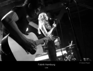 Ivy Flindt on stage at Fabrik, Hamburg. Cate Martin in the background is wearing a beautiful black dress. Micha Holland is playing an acoustic guitar.