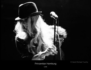 Cate Martin dressed in black wearing a hat and a beautiful silver bracelet live on stage at Prinzenbar, Hamburg.