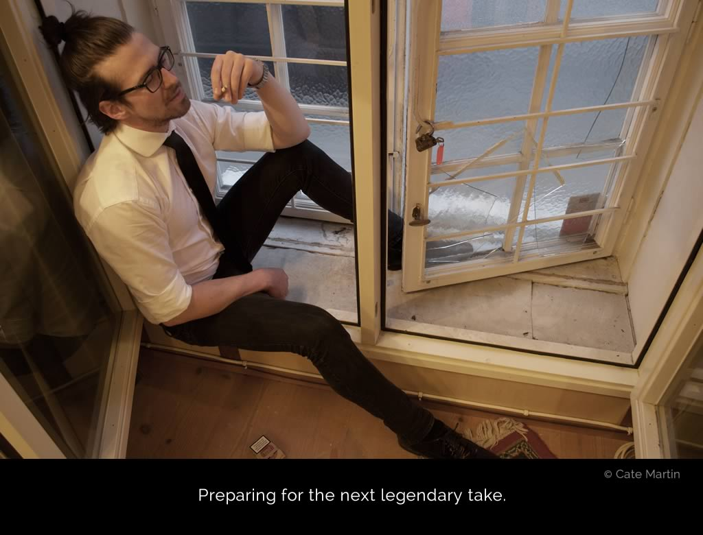 Micha Holland wearing black pants, a white shirt, and a black tie sitting in an open window, having a cigarette before the next guitar recording.