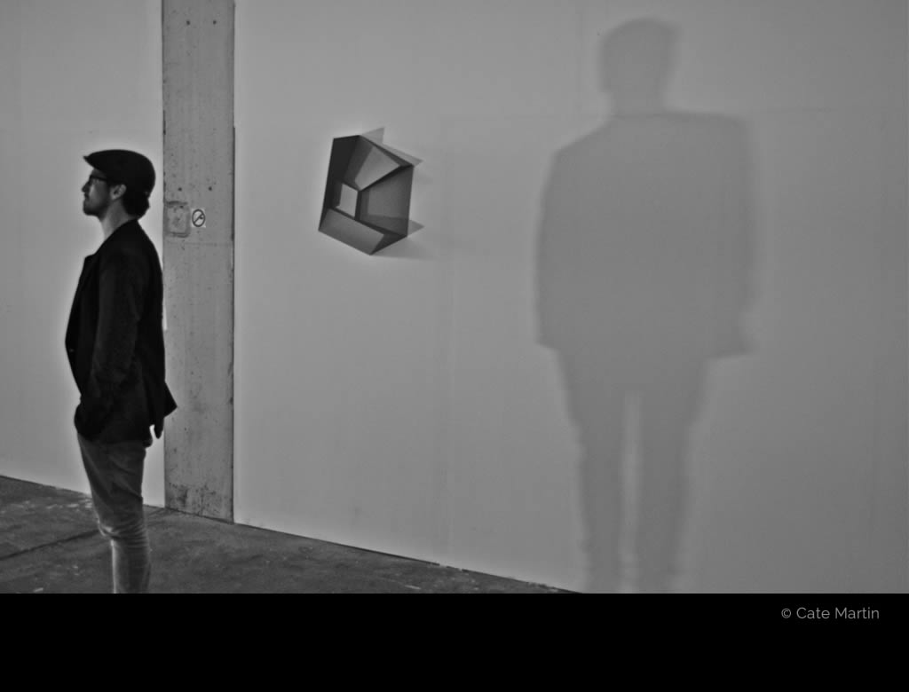 Man with his shadow by Cate Martin. The black-and-white photo shows Micha Holland and his shadow on the wall behind him.