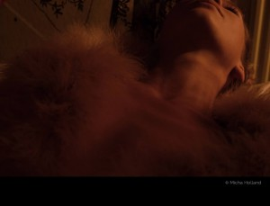Woman lying on her back by Micha Holland. A colour photo showing a woman lying on her back wearing a feather vest.