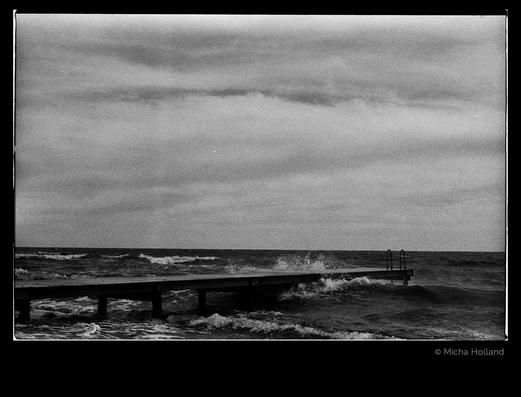 Bathing jetty by Micha Holland. The black-and-white photo shows a bathing jetty leading into rough autumn sea.